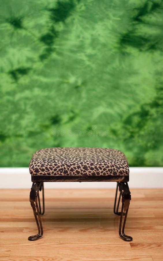 Tabouret de peau de léopard et fond vert photographie stock libre de droits