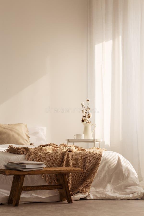 Tabouret en bois devant le lit avec la couverture dans l'intérieur blanc naturel de chambre à coucher avec l'usine photo stock