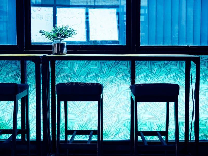 Tabourets de bar de silhouette et contre- barre en bois près du verre de fenêtre sur la pièce légère bleue photographie stock