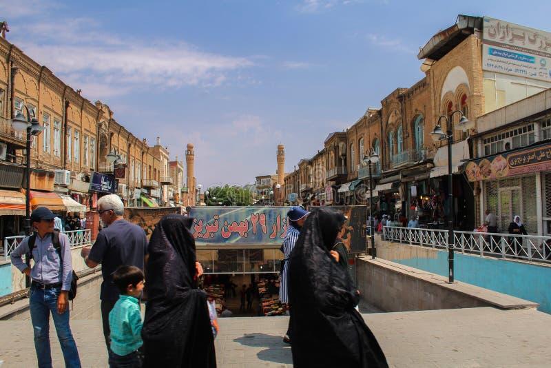 Tabriz, Iran - 10 2017 Lipiec: Irańskie kobiety chodzi w ulicie z czarnym burka w rynku Tabriz z arabską kolumną fotografia royalty free