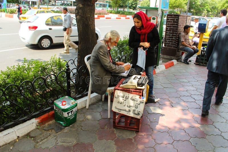 Tabriz, Iran - 10 2017 Lipiec: Stary irański writter w ulicie z jego maszyną do pisania bierze notatki irańska kobieta obrazy royalty free