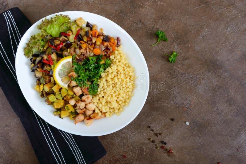 Tabulé orientale delizioso dell'insalata Cuscus con le verdure ed il pollo fritti su un piatto bianco immagine stock