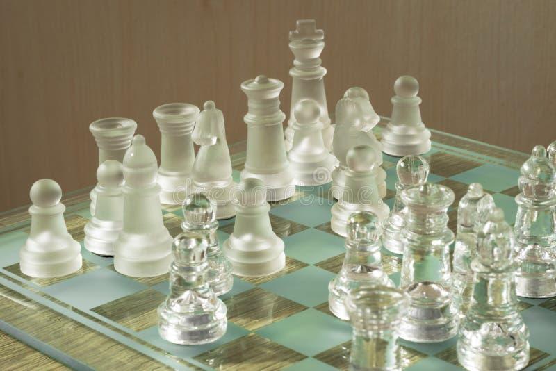 Tabuleiro de xadrez e partes feitos do vidro fotografia de stock