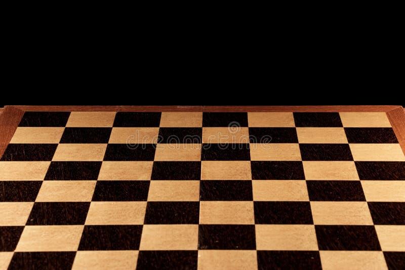 Tabuleiro de xadrez vazio em um fundo preto foto de stock