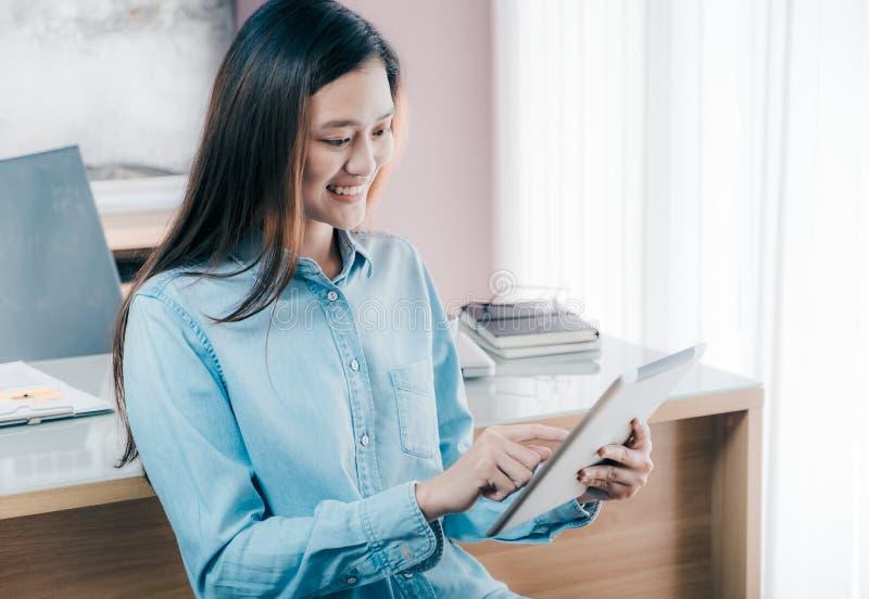 Tabuleta asiática do uso da mulher de negócios à reunião em linha da conferência com fotografia de stock royalty free
