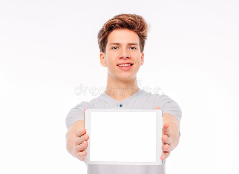 Tabuleta atrativa da terra arrendada do adolescente do estudante do homem novo com a tela branca, isolada no fundo branco, modelo foto de stock