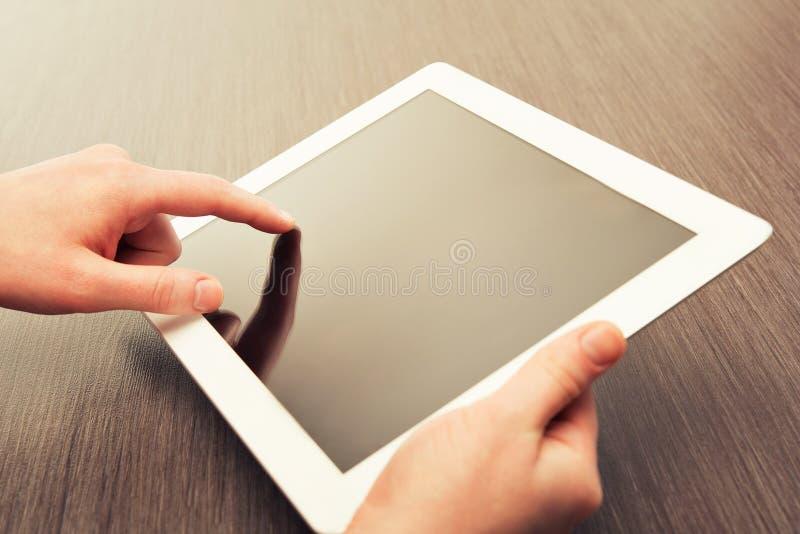 Tabuleta branca com uma tela vazia nas mãos na tabela