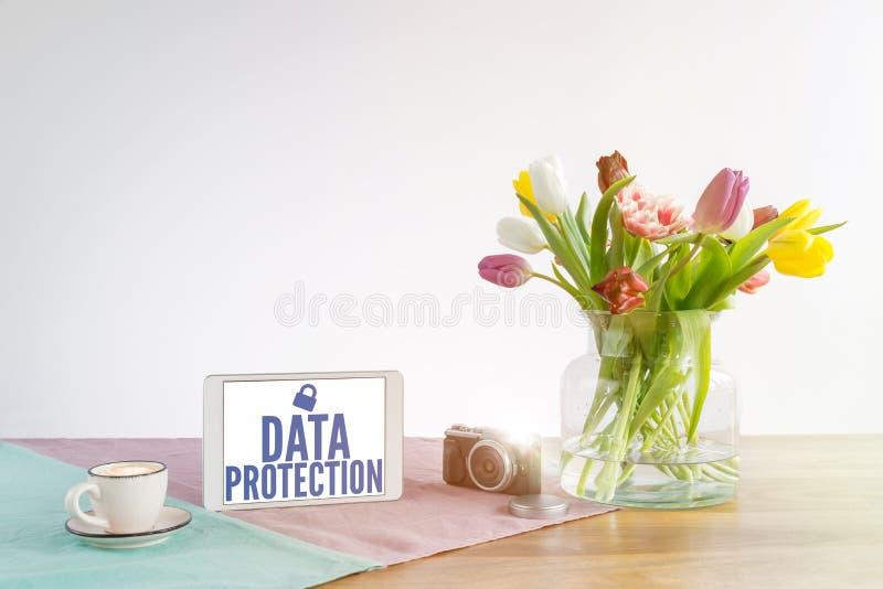 Tabuleta com escrita da proteção de dados na mesa de madeira com vagabundos brancos imagem de stock