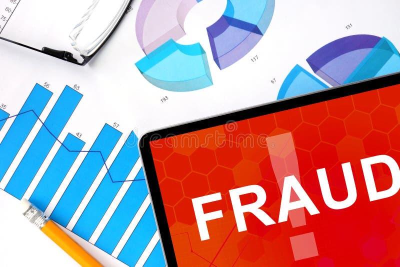 Tabuleta com fraude e gráficos da palavra fotografia de stock