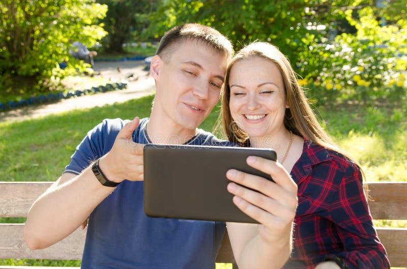 Tabuleta da terra arrendada do homem novo em suas mãos e apontar à menina de sorriso da tela de que se está sentando ao lado foto de stock royalty free