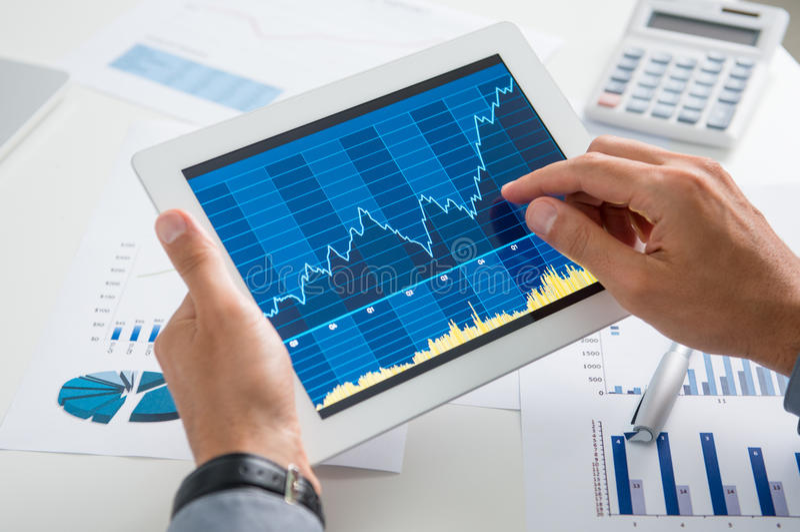 Tabuleta de Analysing Growth With do homem de negócios fotografia de stock royalty free