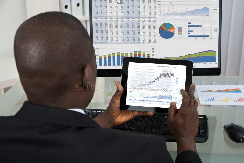 Tabuleta de Analyzing Graph On Digital do homem de negócios imagem de stock