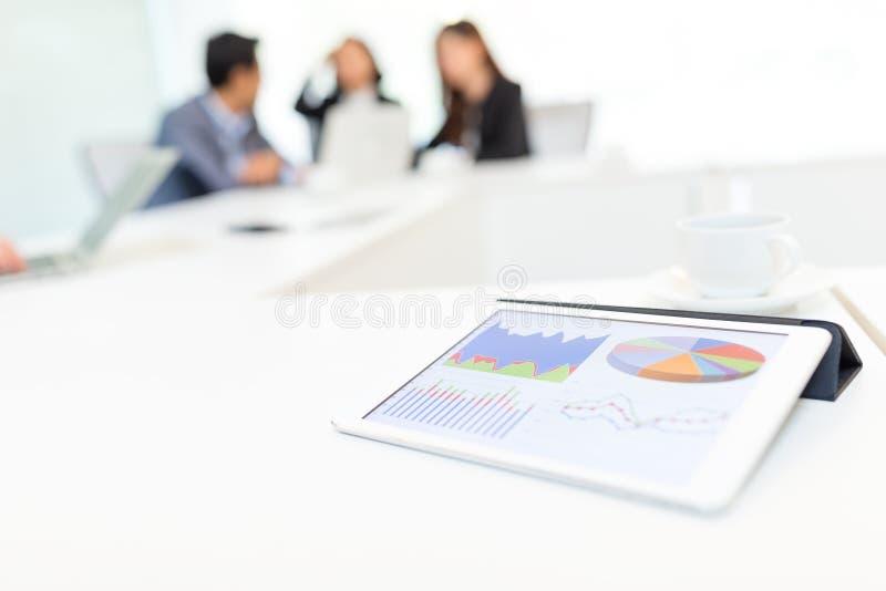 Tabuleta de Digitas que mostra a carta dos dados na tela na reunião de negócios fotografia de stock royalty free
