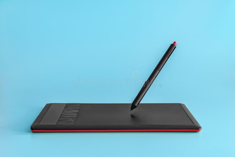 tabuleta de gráficos e estilete Preto-vermelhos levitar em um claro - fundo azul fotografia de stock