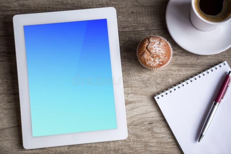 Tabuleta de Ipad com a xícara de café sobre a tabela de madeira imagens de stock