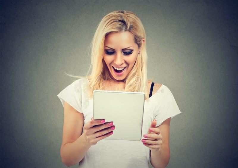 Tabuleta de observação da jovem mulher entusiasmado fotografia de stock