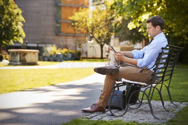 Tabuleta de Outdoors Using Digital do homem de negócios na pausa para o almoço no parque fotografia de stock