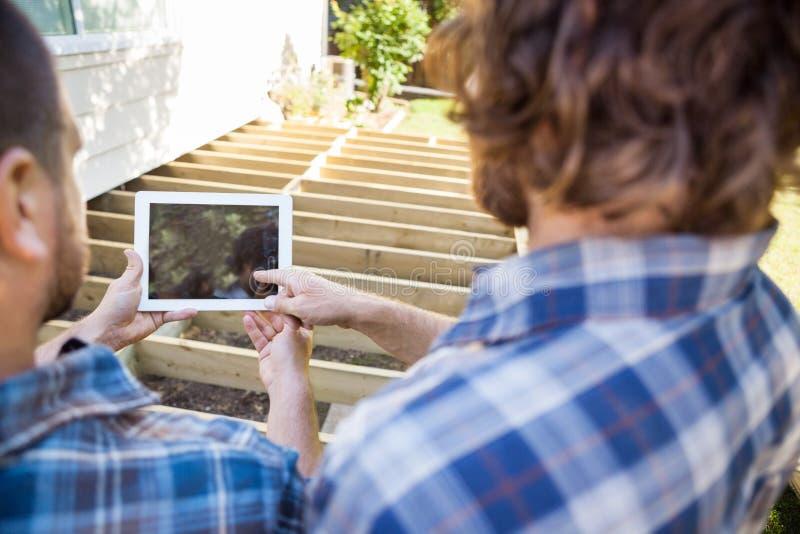 Tabuleta de Pointing At Digital do carpinteiro quando fotografia de stock royalty free
