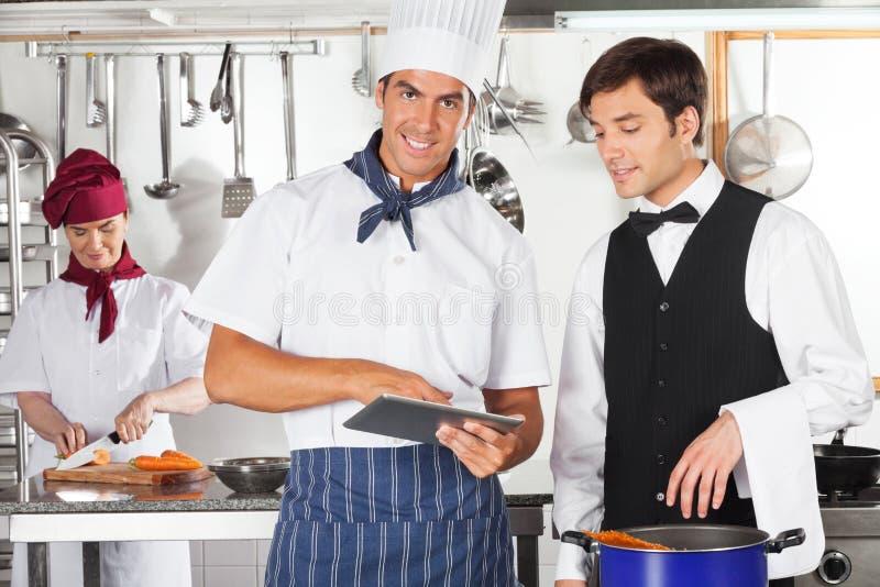 Tabuleta de With Waiter Using Digital do cozinheiro chefe fotografia de stock royalty free