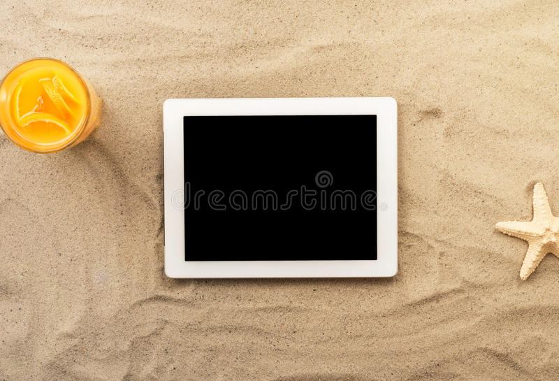Tabuleta digital branca com espaço da cópia na areia foto de stock royalty free