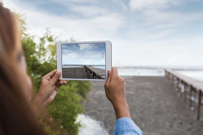 Tabuleta digital do uso da mulher que toma a imagem da paisagem fotografia de stock