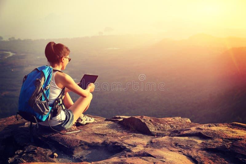 Tabuleta digital do uso do caminhante da mulher na montanha fotografia de stock royalty free