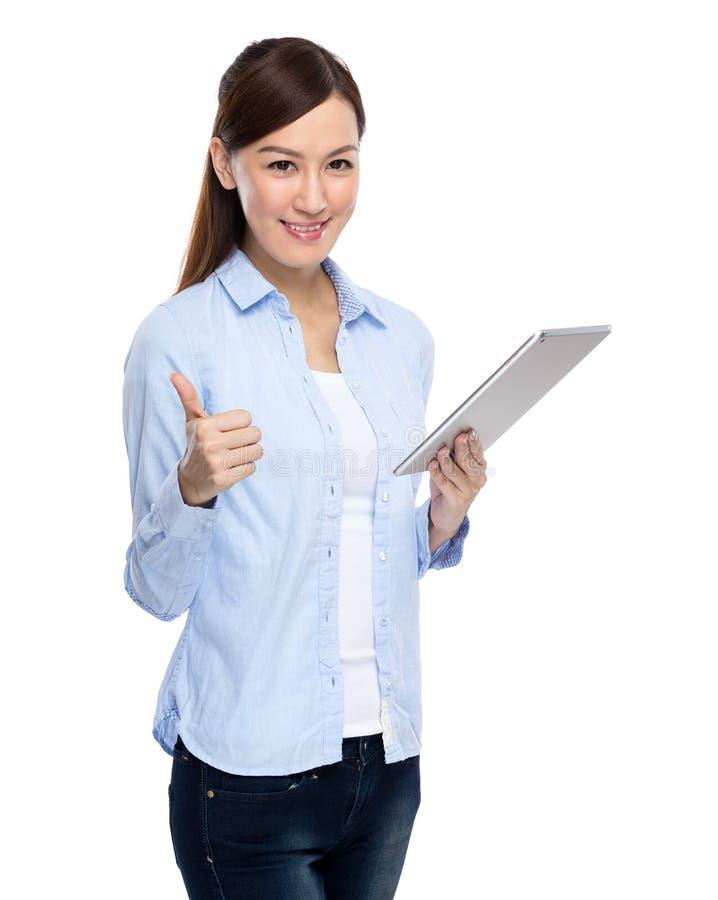 Tabuleta digital e polegar do uso asiático da mulher acima fotografia de stock