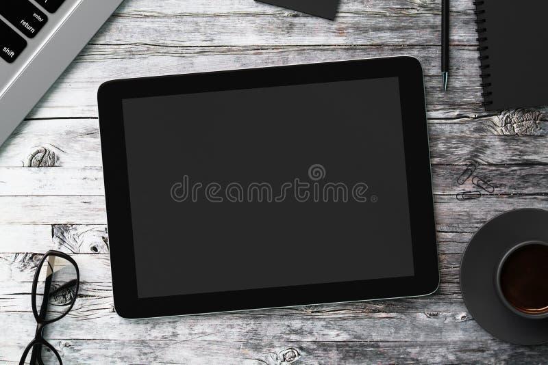 Tabuleta digital preta vazia em uma tabela de madeira imagem de stock royalty free