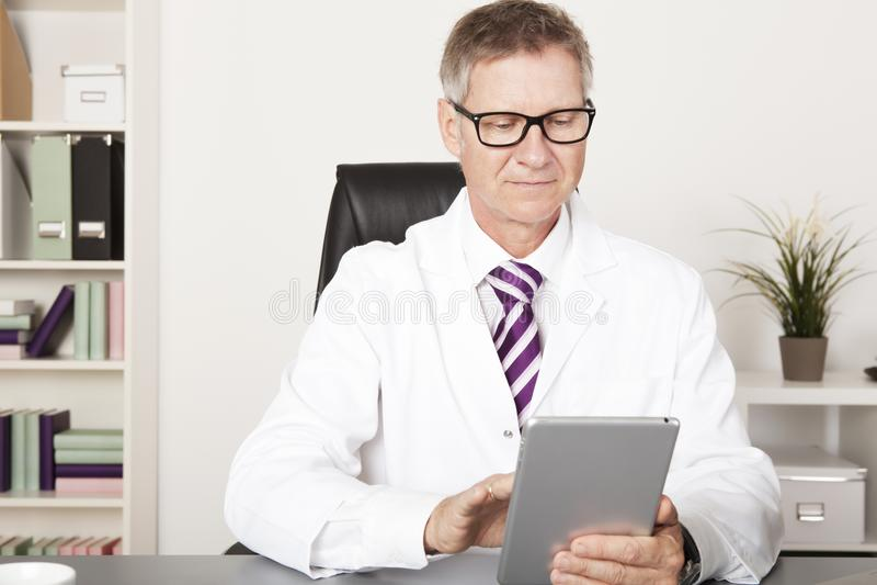 Tabuleta do médico Reading Reports Using fotos de stock