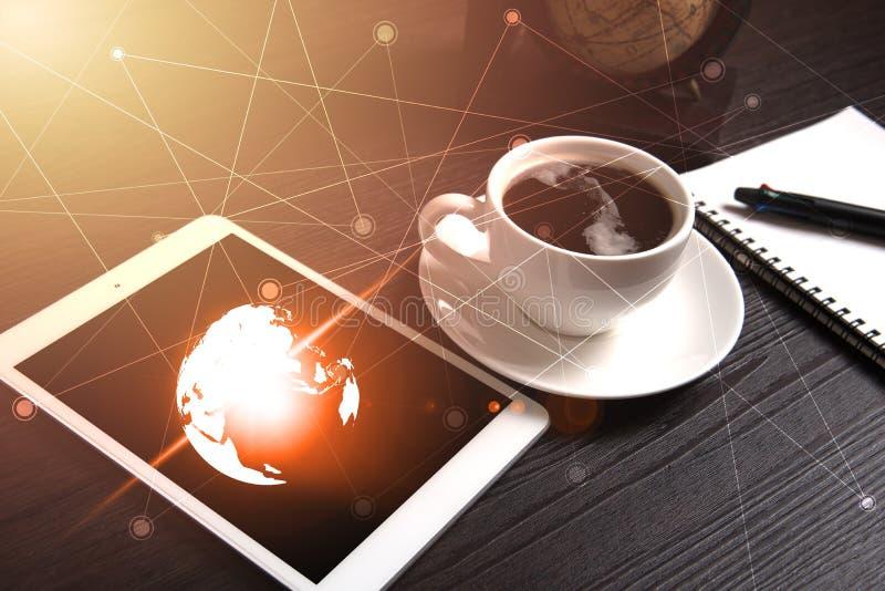 Tabuleta e café preto na tabela de madeira com o mapa do mundo da terra de Digitas e luz alaranjada e linha ponto, caderno e pena imagens de stock