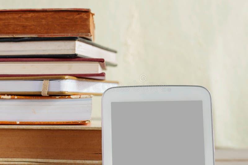 Tabuleta e livros em de madeira foto de stock