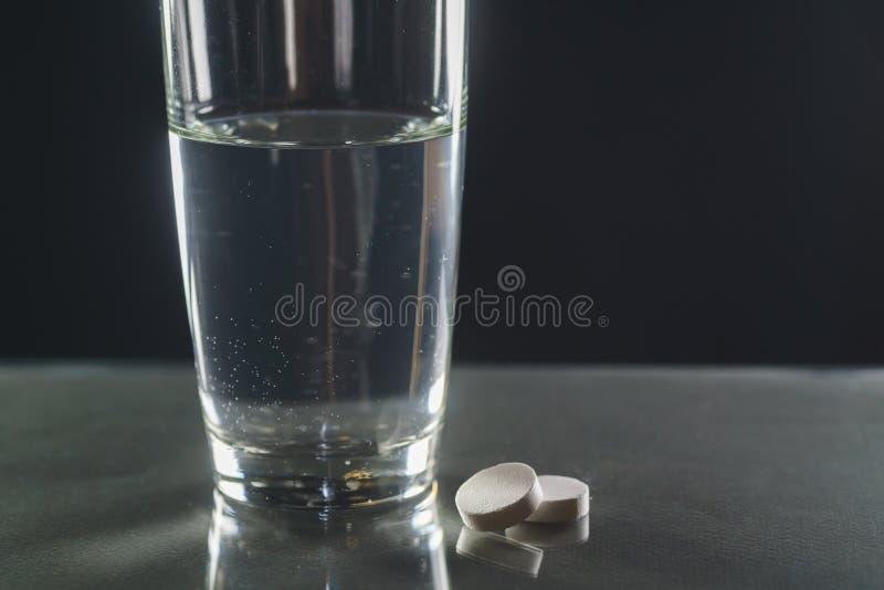 Tabuleta Effervescent na água com bolhas fotografia de stock