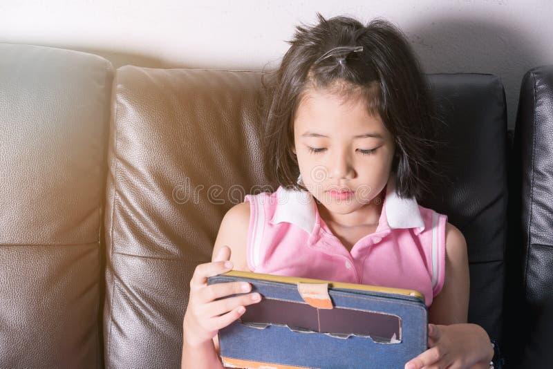Tabuleta feliz do jogo da menina de Ásia imagem de stock