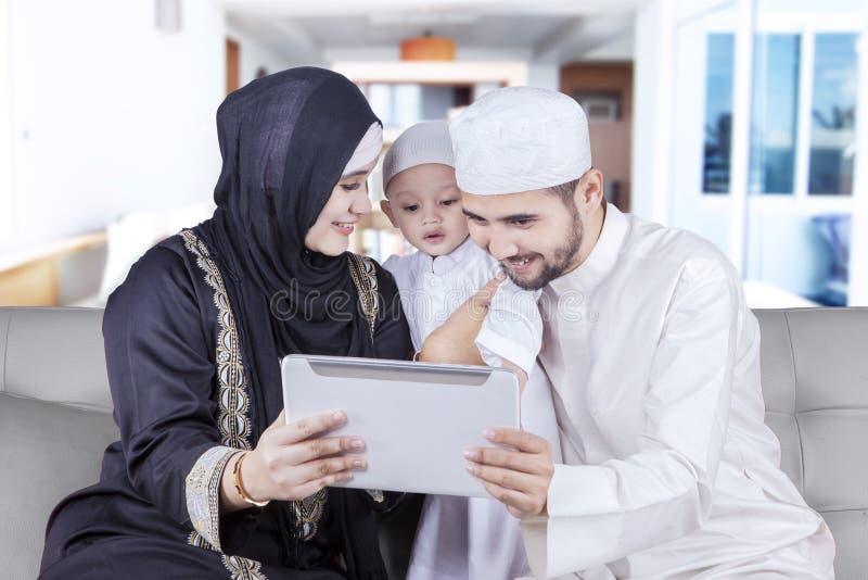 Tabuleta muçulmana feliz do uso da família no sofá imagem de stock royalty free