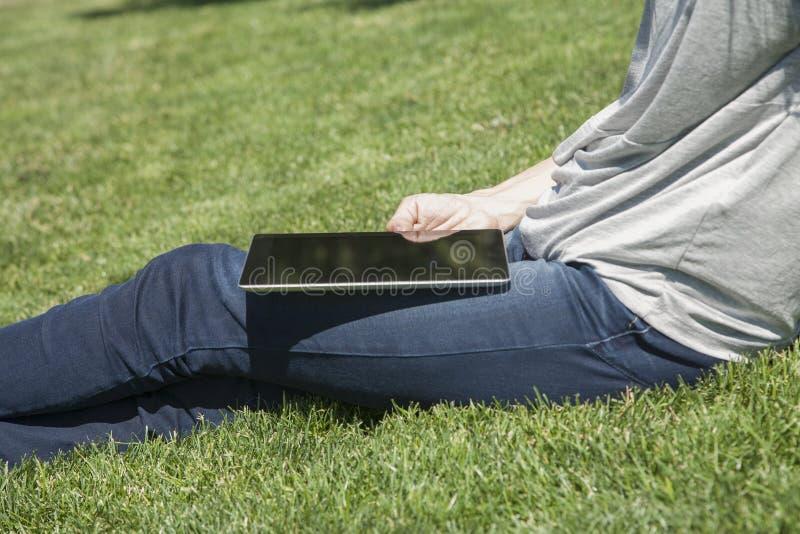 Tabuleta nos pés que sentam-se na grama foto de stock
