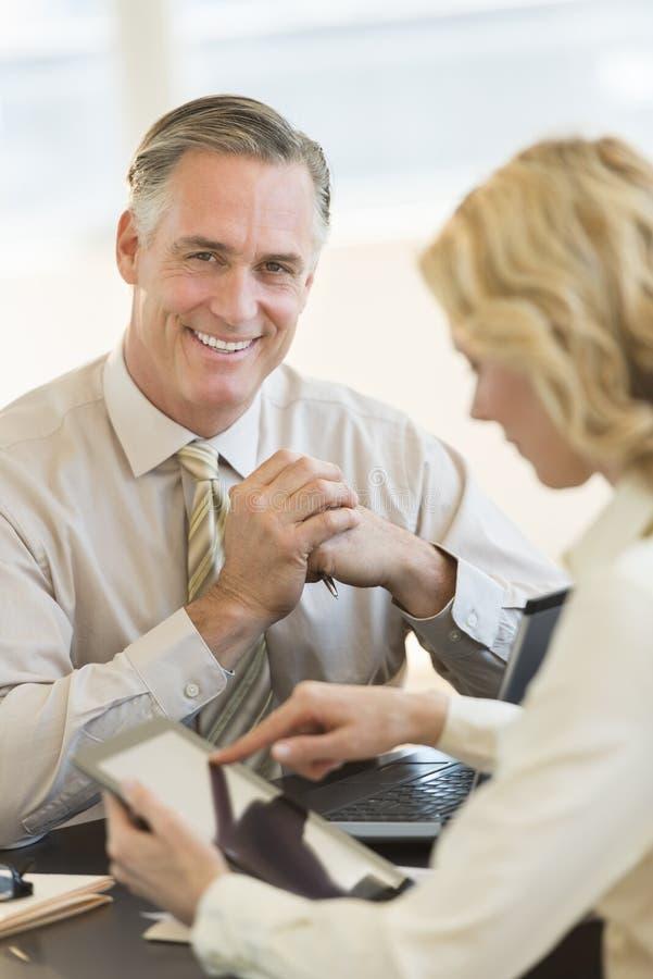 Tabuleta segura de With Coworker Using Digital do homem de negócios em Offi imagens de stock royalty free