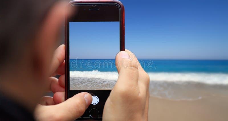A tabuleta, smartphone no ` s do homem entrega a tomada da imagem do litoral arenoso Fundo borrado imagens de stock royalty free