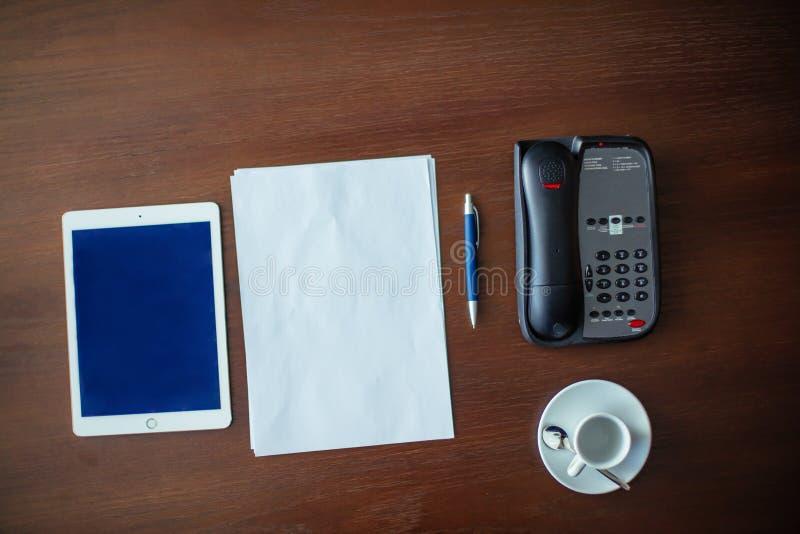 Tabuleta, telefone celular e uma xícara de café na mesa foto de stock