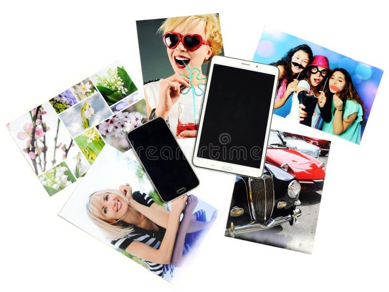 Tabuleta, telefone e fotos impressas fotografia de stock