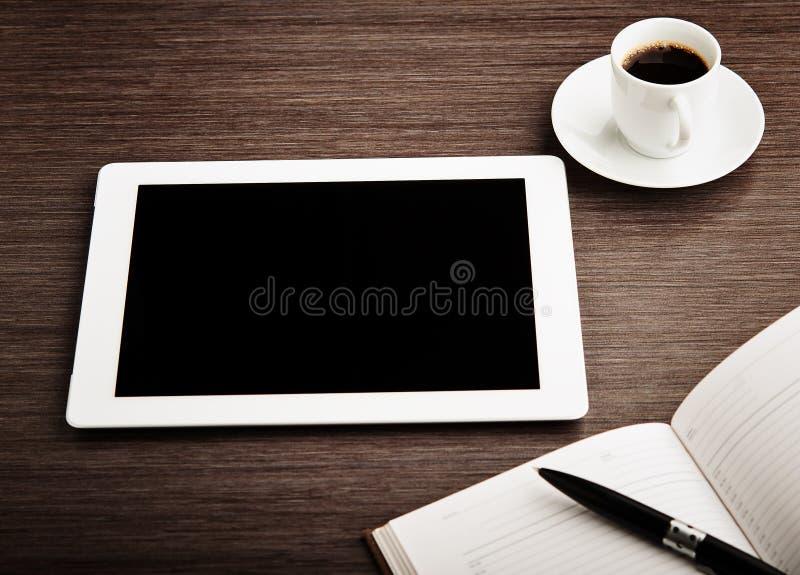 Tabuleta vazia e um café na mesa imagens de stock