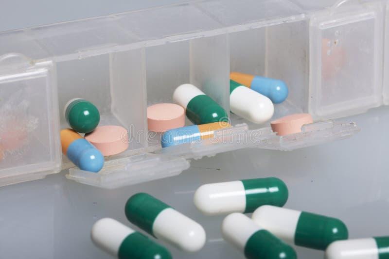 Tabuleta virada com medicinas Na tabela tabuletas e comprimidos coloridos dispersados Em um fundo branco fotos de stock