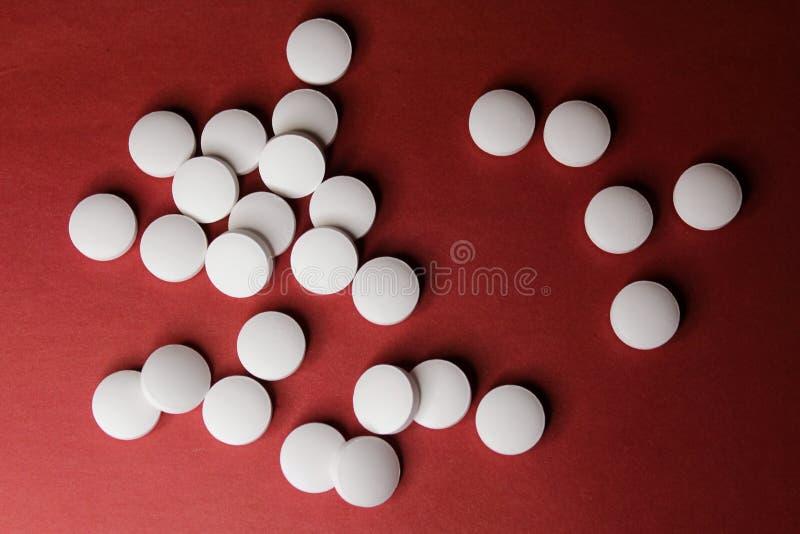 Tabuletas brancas do círculo médico, close up das vitaminas do cálcio no fundo vermelho com espaço para o texto ou imagem Comprim imagem de stock royalty free