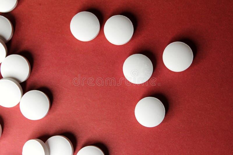 Tabuletas brancas do círculo médico, close up das vitaminas do cálcio no fundo vermelho com espaço para o texto ou imagem Comprim imagem de stock