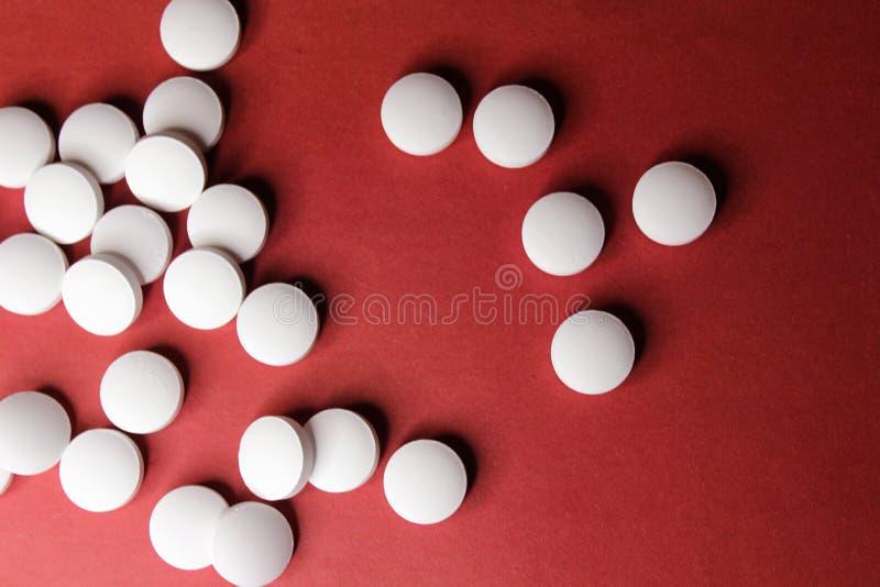 Tabuletas brancas do círculo médico, close up das vitaminas do cálcio no fundo vermelho com espaço para o texto ou imagem Comprim fotografia de stock