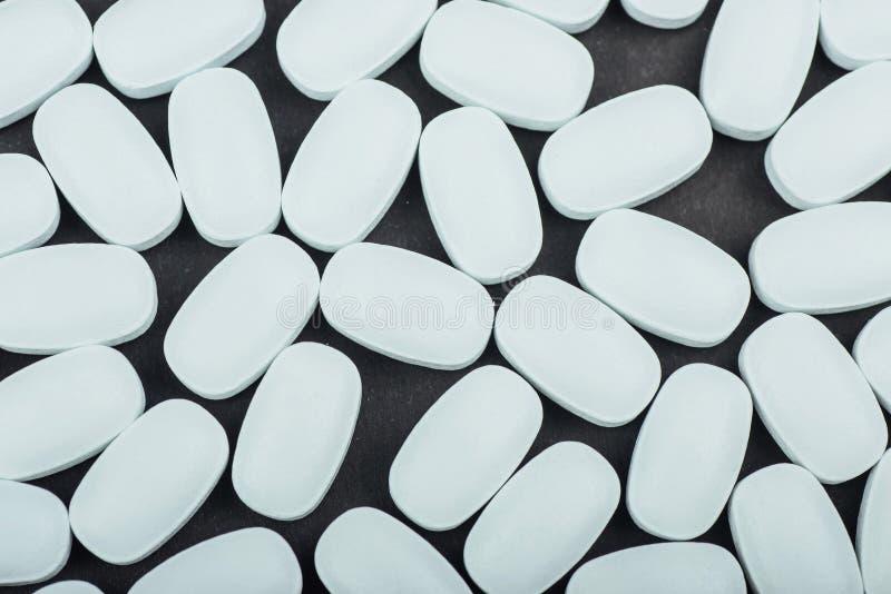 Tabuletas brancas médicas ou suplementos para o tratamento e os cuidados médicos em um fundo preto foto de stock