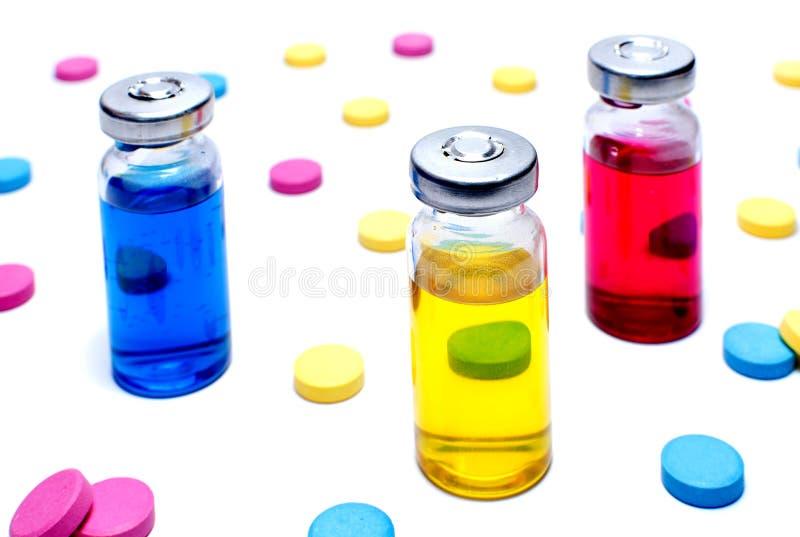 Tabuletas coloridos e vacinas contra no branco imagens de stock