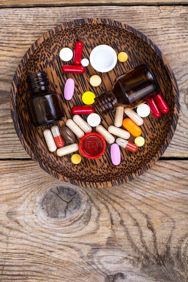 Tabuletas, comprimidos e cápsulas diferentes no fundo de madeira foto de stock