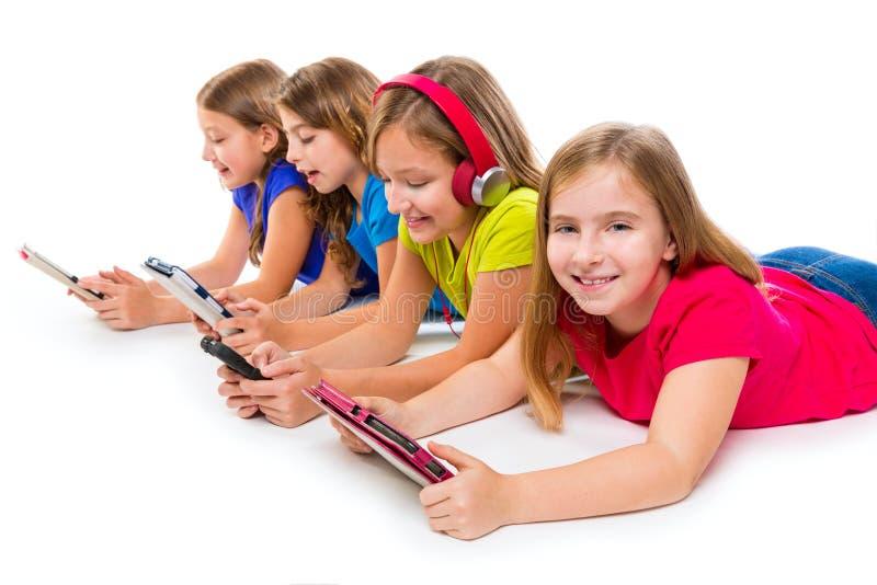 Tabuletas e smatphones da tecnologia das meninas da criança das irmãs foto de stock