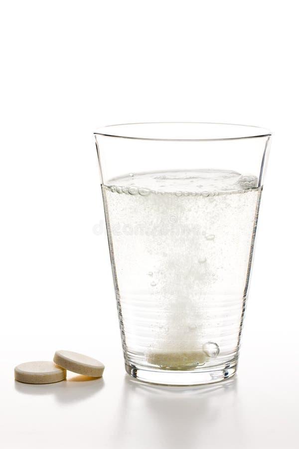 Tabuletas e vidro Effervescent com água foto de stock royalty free