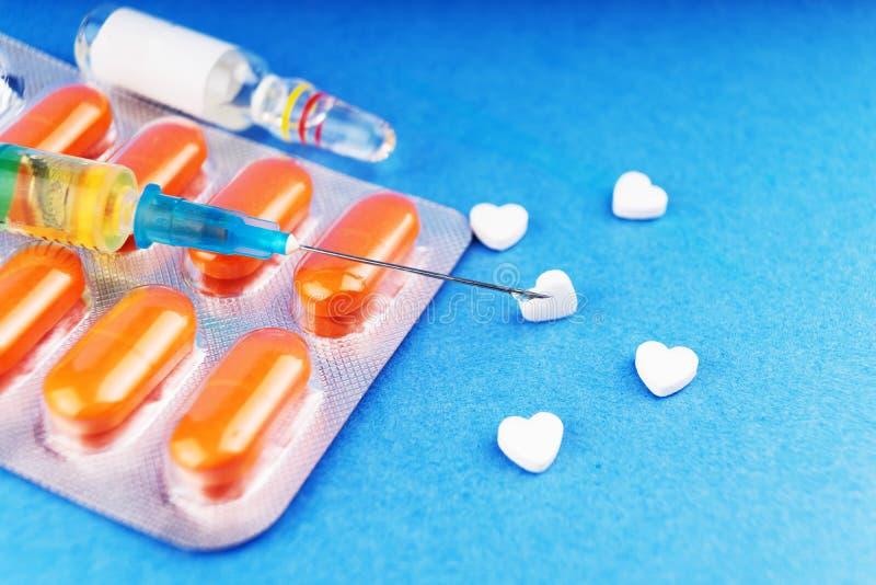 Tabuletas em uma bolha, uma seringa com o preparati médico datilografado fotos de stock